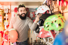 Man deciding on new helmet. Positive guy deciding on new helmet in sports equipment store Stock Photography