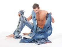 Man deciding what to wear. Cool shirtless trendy man in a pair of modern ragged jeans sitting deciding what to wear Royalty Free Stock Photo