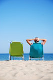 Man on deckchair at the beach. Man relaxing on sunbed at tropical beach Royalty Free Stock Photos