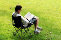 Man in deckchair reading. Outdoor portrait of man reading royalty free stock photo