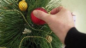 Man decorates a Christmas tree. stock video