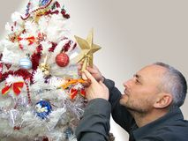 Man decorating Christmas tree Stock Image