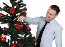 Man decorating the Christmas tree. A young man decorating a Christmas tree isolated against a white background Stock Image