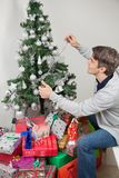 Man Decorating Christmas Tree With Fairy Lights At Royalty Free Stock Photography