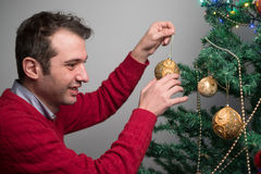Man decorating a christmas tree with golden balls stock images