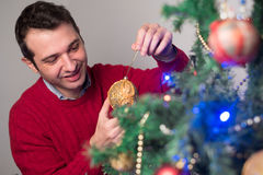 Man decorating a christmas tree with golden balls Stock Image