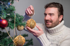 Man decorating a christmas tree with golden balls Royalty Free Stock Images