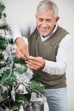 Man Decorating Christmas Tree With Silver Stock Photo