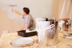Man Decorating Room Using Paint Roller On Wall Stock Image