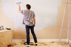 Man Decorating Room Using Paint Roller On Wall Stock Photography