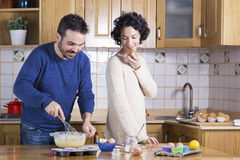 Man deeg zwaaien en vrouw die eigengemaakte cupcakes eten Stock Foto's