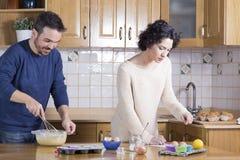 Man deeg zwaaien en vrouw die recept van eigengemaakte cupca bekijken Royalty-vrije Stock Foto