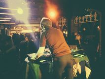 Man deejaying records at a nightclub. A male DJ is playing records at a nightclub in front of the dance floor Stock Photos
