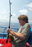 Man deep sea fishing. Pulling on the rod to catch a fish Royalty Free Stock Photos