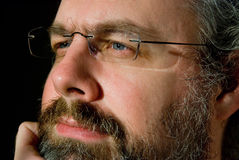 Man in deep thought. A Caucasian man with glasses and beard in thought.  Partial view of face showing eyes, nose and mouth Royalty Free Stock Photo