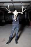 Man with deer skull for a head in dark basement Stock Photo