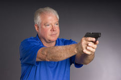 Man Defends Himself Holding Pointing Small Semi Au. Man points small caliber semi automatic handgun to off camera right Stock Photo