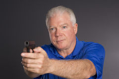 Man Defends Himself Holding Pointing Small Semi Automatic Handgun. Man points small caliber semi automatic handgun to off camera left Stock Photo