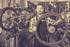 Man define a bicycle wheel. Smiling young man define a bicycle wheel in a bicycle shop Stock Photography