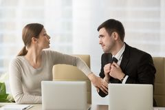 Businessman asking female colleague about favor. Man with deliberately sad facial expression asking female coworker to help with difficult project to leave work stock images