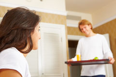 Man delivering breakfast to her spouse in bed Stock Photography
