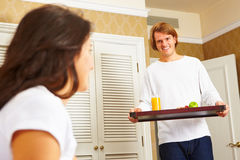 Man delivering breakfast to her spouse in bed Stock Images