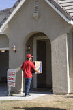 Man Delivering Cardboard Box Into New House Stock Photo
