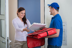 Man Delivering Pizza To Young Woman Stock Photography