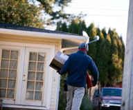 Man delivers parcel box to house at delivery address Stock Images