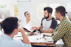 A man demonstrates business graphics. His collegues are listening to him. A group of young people discussing business. They working in the office. A men Stock Photo
