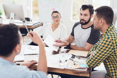 A man demonstrates business graphics. His collegues are listening to him. A group of young people discussing business. They working in the office. A men Stock Photography