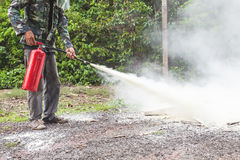 A man demonstrating how to use a fire extinguisher Stock Image