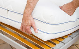 Man demonstrating quality of mattress Stock Image