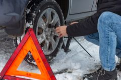 Man demontaging a car wheel on a snow road. Ð•mergency sign royalty free stock photo