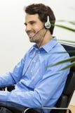 Man den bärande hörlurar med mikrofon som ger online-pratstund och, stötta arkivbilder