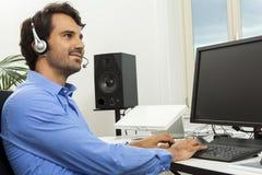 Man den bärande hörlurar med mikrofon som ger online-pratstund och, stötta fotografering för bildbyråer