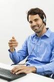 Man den bärande hörlurar med mikrofon som ger online-pratstund och, stötta royaltyfria bilder