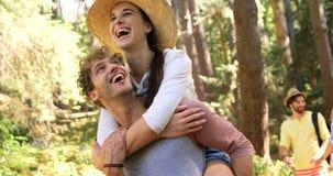 Man den bärande kvinnan på hans skuldra och andra parinnehavhänder lager videofilmer