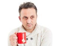 Man den bärande stack sweatern som rymmer en råna av varmt te Arkivfoto