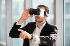 Man den bärande VR-hörlurar med mikrofon och att peka på luften Royaltyfri Fotografi