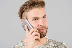 Man den fundersamma drömlika brukssmartphonekommunikationen, grå bakgrund svart telefon för kommunikationsbegreppsmottagare Ansad arkivbild