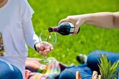 Man den hällande kvinnan per exponeringsglas av rött vin på picknicken Royaltyfri Foto