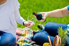 Man den hällande kvinnan per exponeringsglas av rött vin på picknicken Arkivfoto