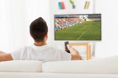 Man den hållande ögonen på fotboll- eller fotbollleken på tv hemma Fotografering för Bildbyråer