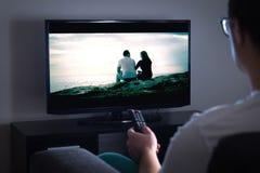 Man den hållande ögonen på tv eller tryckningsfilmen eller serien med smart tv royaltyfria bilder