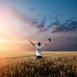 Man den hållande övre bibeln i ett vetefält Fotografering för Bildbyråer