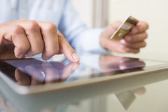 Man den hållande den inomhus minnestavlaPC:n och kreditkorten, online-shopping Arkivfoto
