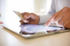 Man den hållande den inomhus minnestavlaPC:n och kreditkorten, online-shopping Royaltyfri Foto