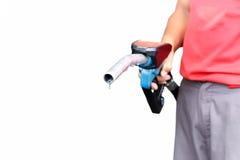 Man den hållande dysan för bensinpumpen med isolerad droppe av fossila bränslen Arkivfoto
