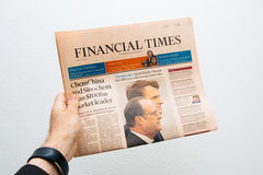 Man den hållande Financial Times tidningen med Emmanuel Macron på fi Arkivfoton
